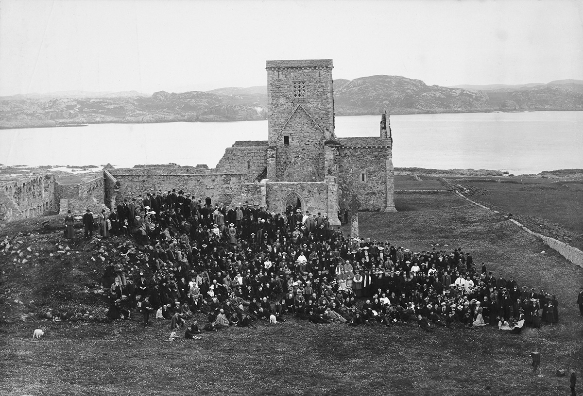 A large crowd is gathered in front of Iona Abbey. The photo is black and white and the sea and Isle of Mull are in the background.