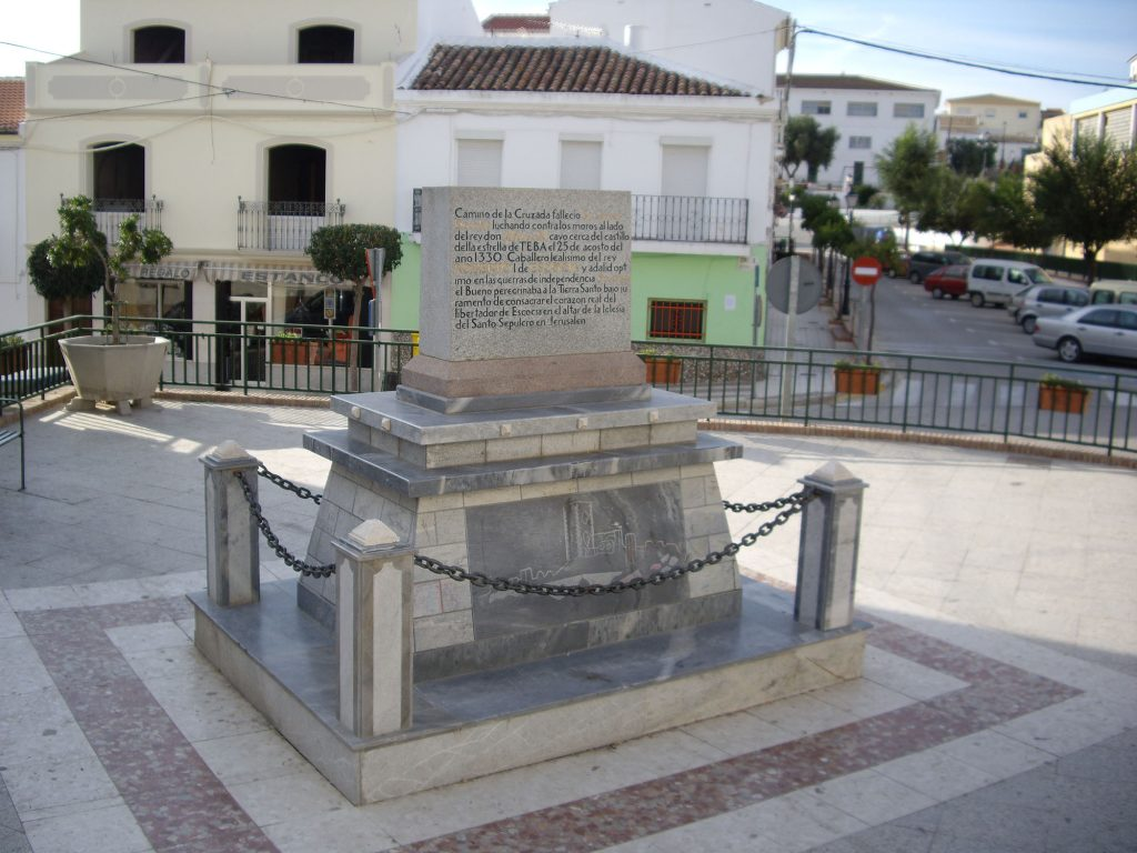 A stone monument in surrounded by a low chain fence. There is an inscription in black and gold writing on the front of the monument. Buildings typical of southern Spain are in the background.