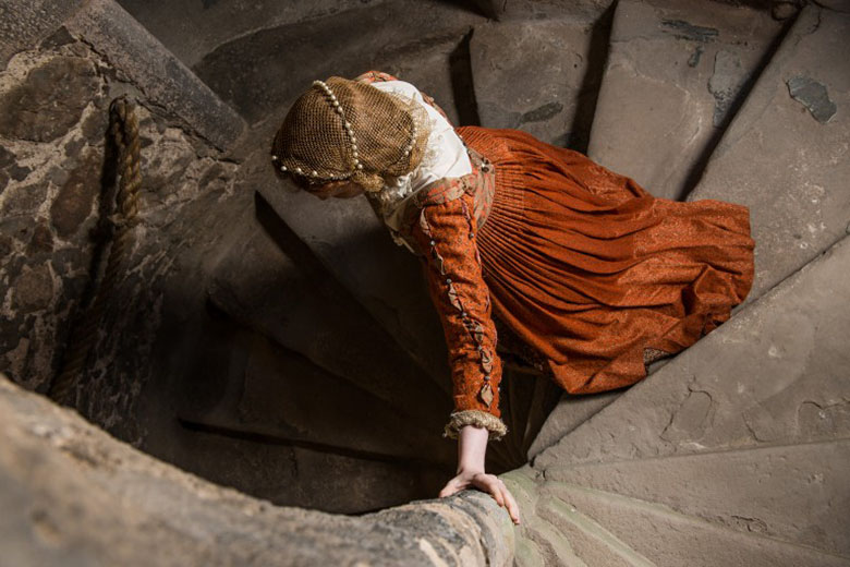 A model dressed as Mary Queen of Scots walks down a stone spiral staircase. She is wearing a red and gold dress.