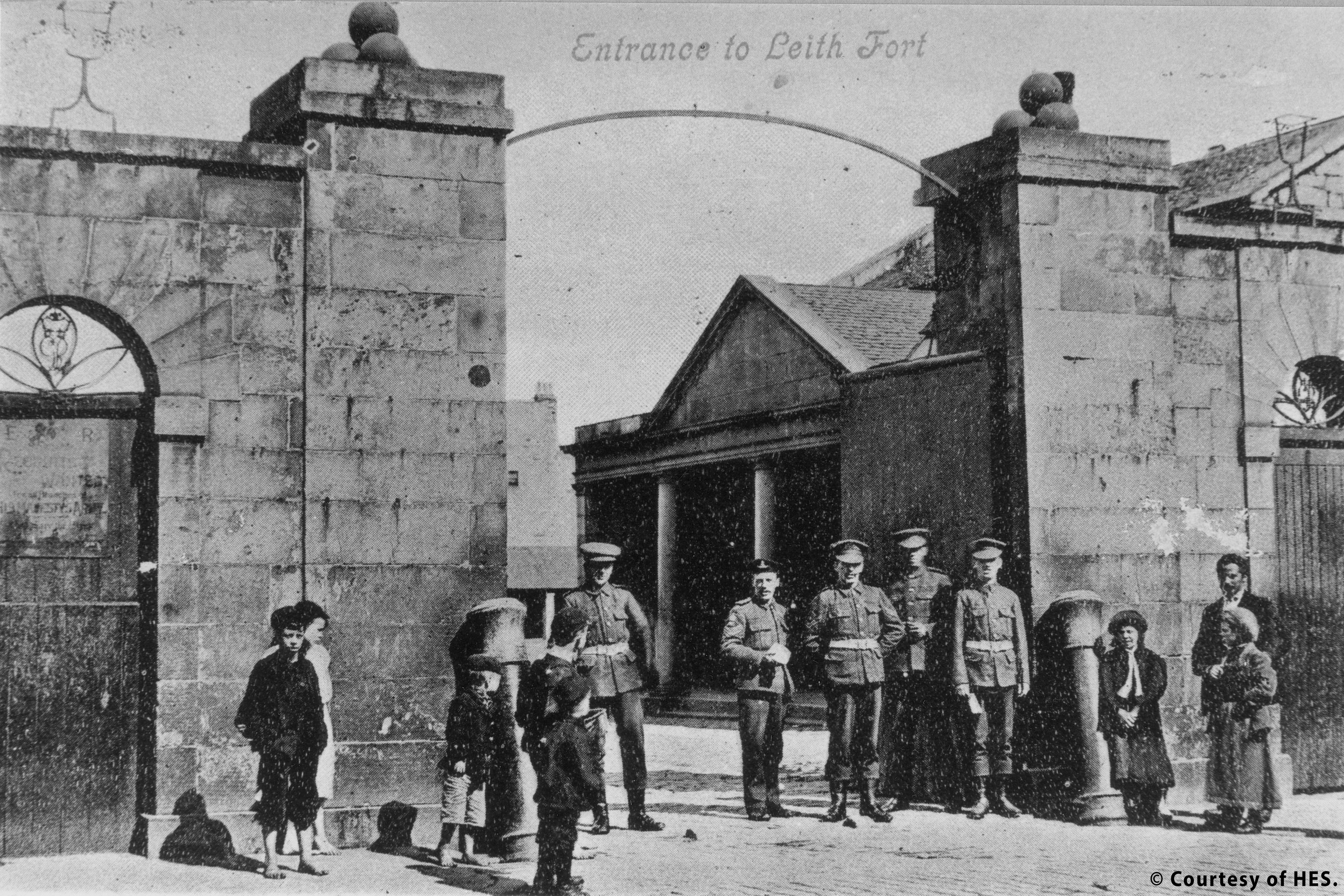 An archive image of the entrance to Leith fort. A large stone gateway is open showing a glimpse of fort buildings. Five soldiers in uniform are standing in the gateway. A number of local children are standing nearby.