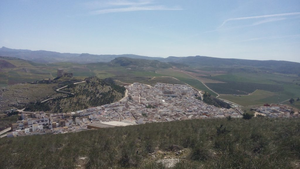 A general view of a Spanish mountain town. There is a ruined castle on a hill overlooking the town.