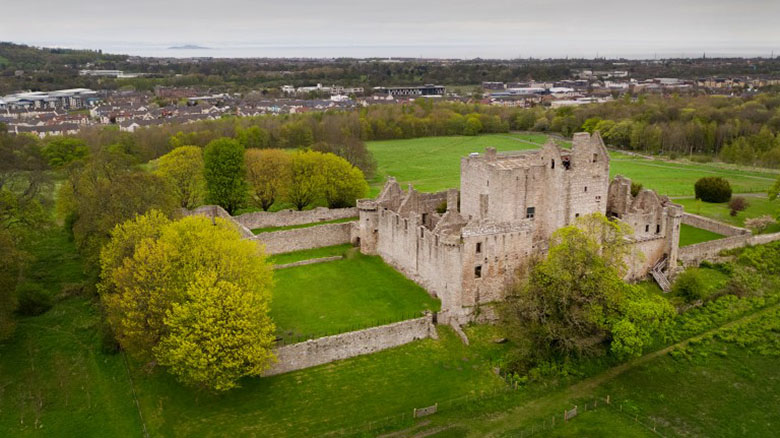 A view of Craigmillar Castle, venue for Spotlight on Mary. The city of Edinburgh and the Firth of Forth can be seen in the background. The castle is surrounded by green fields and trees and a walled garden is evident.