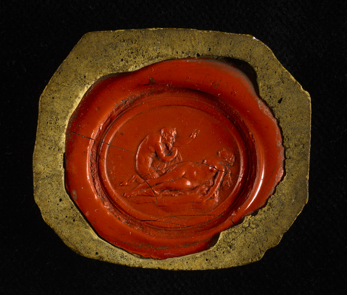 A small red wax seal containing intricate, classical-looking artwork. A nude lady is shown interacting with a bearded man. The man has a tail which suggests this may be a representation of the Devil.
