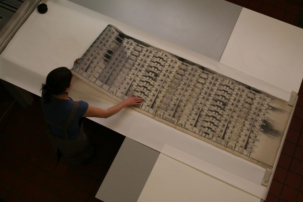 A member of an archives team works on a large architectural drawing by Basil Spence. The drawing is being carefully laid out onto a white table.
