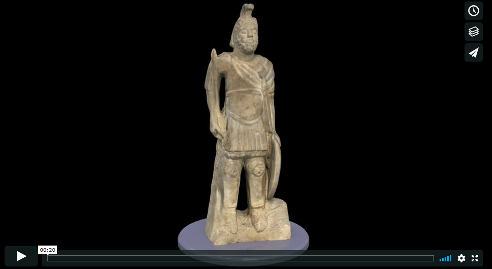 A stone statue of Mars, a Roman God. The statue is of a man wearing Roman-style military uniform. In one hand he holds a circular shield and in the other a sword. He wears a Roman helmet with a plume.