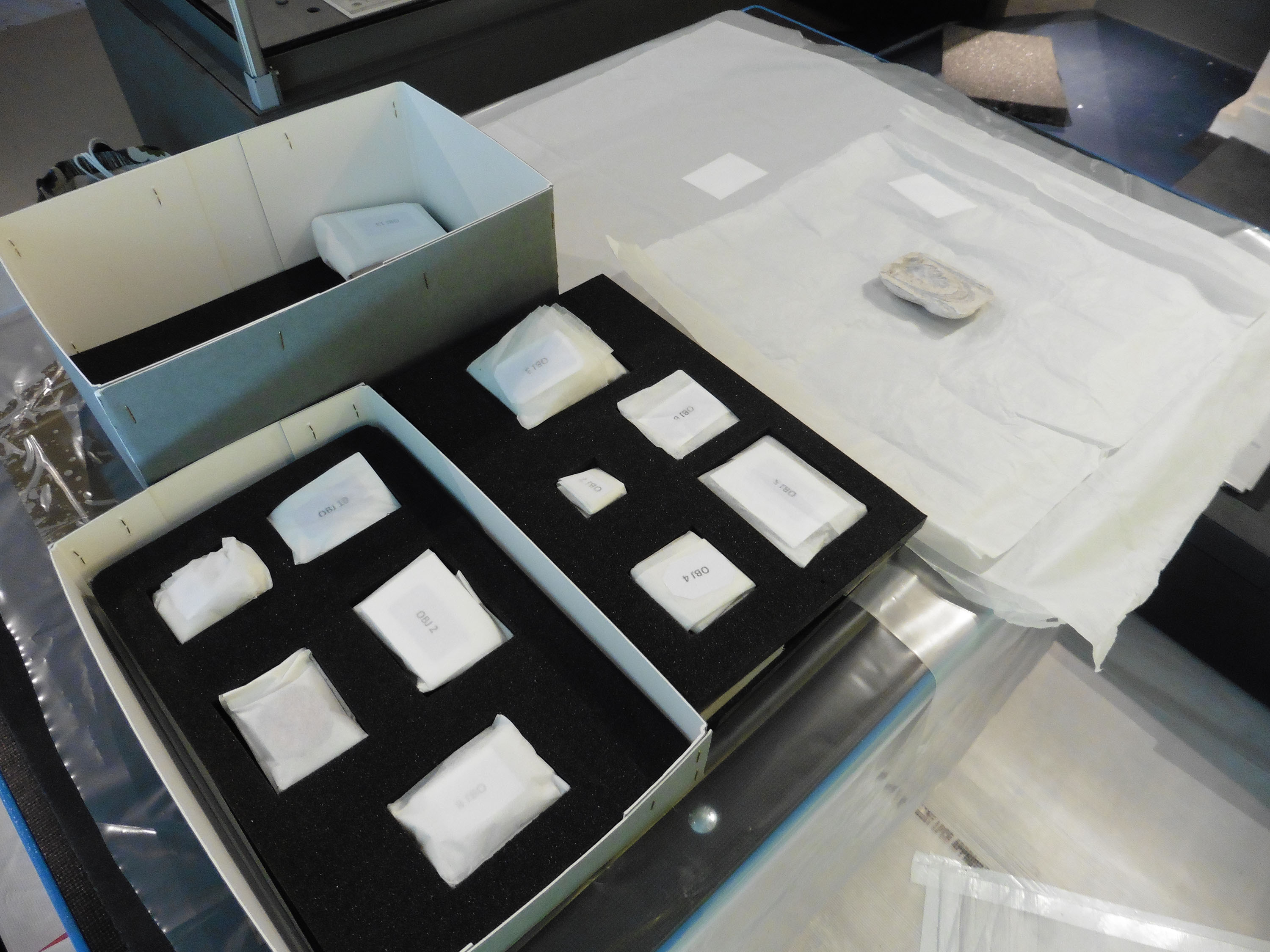 A box of objects is being unpacked on to a table at a museum. Each object is individually numbered and wrapped in white protective material.