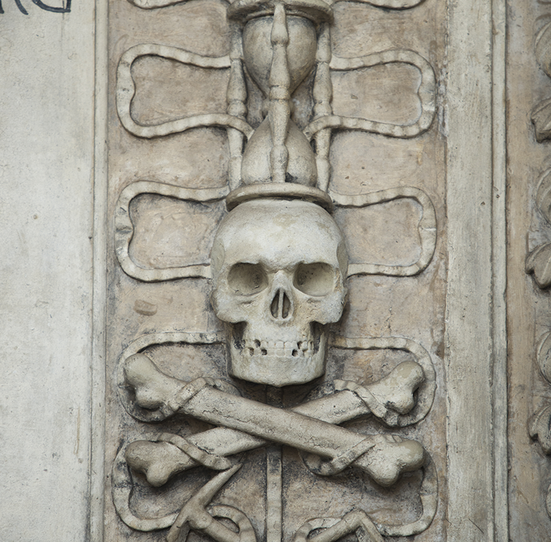 Carving of a skull and crossbones with an hour glass carved above it