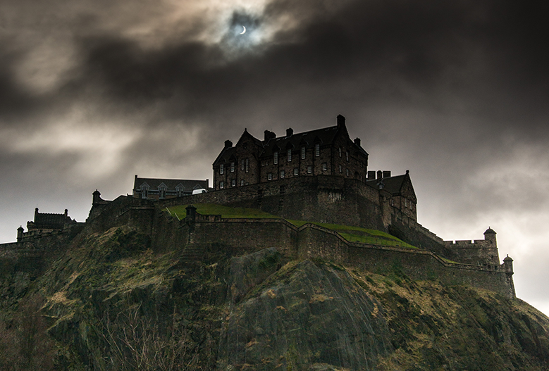 view of edinburghcastle looking spooky during an eclipse