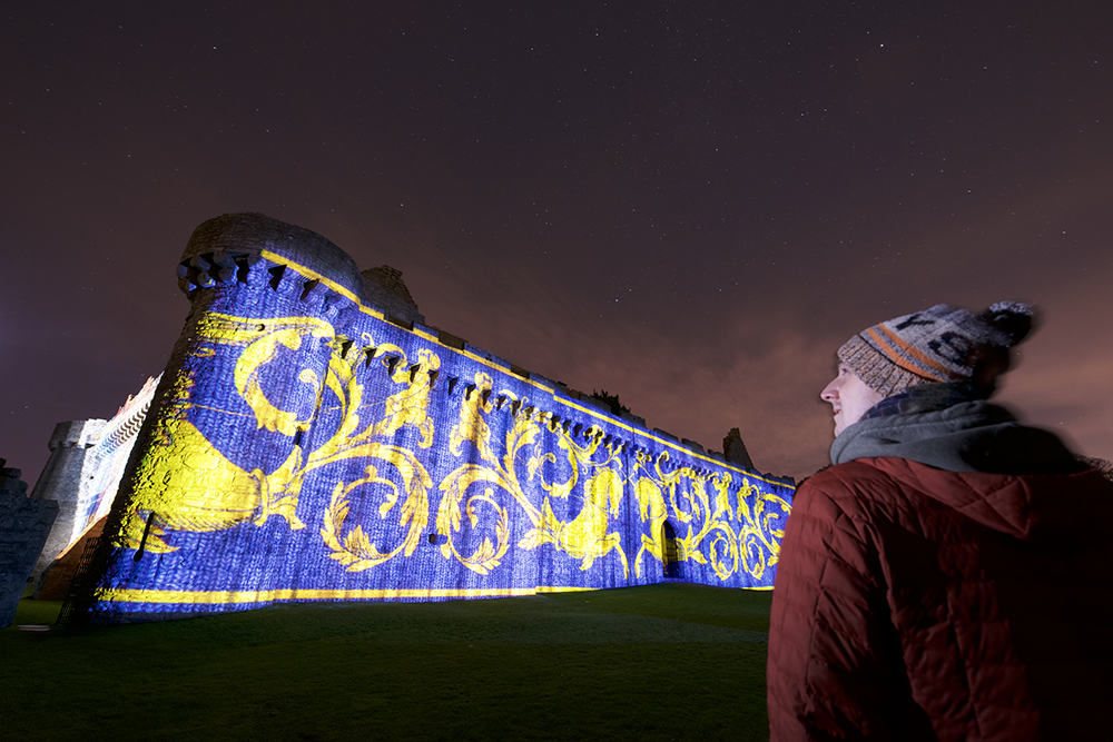 A man looks on as a huge blue and gold pattern is projected onto an exterior wall of Craigmillar Castle.