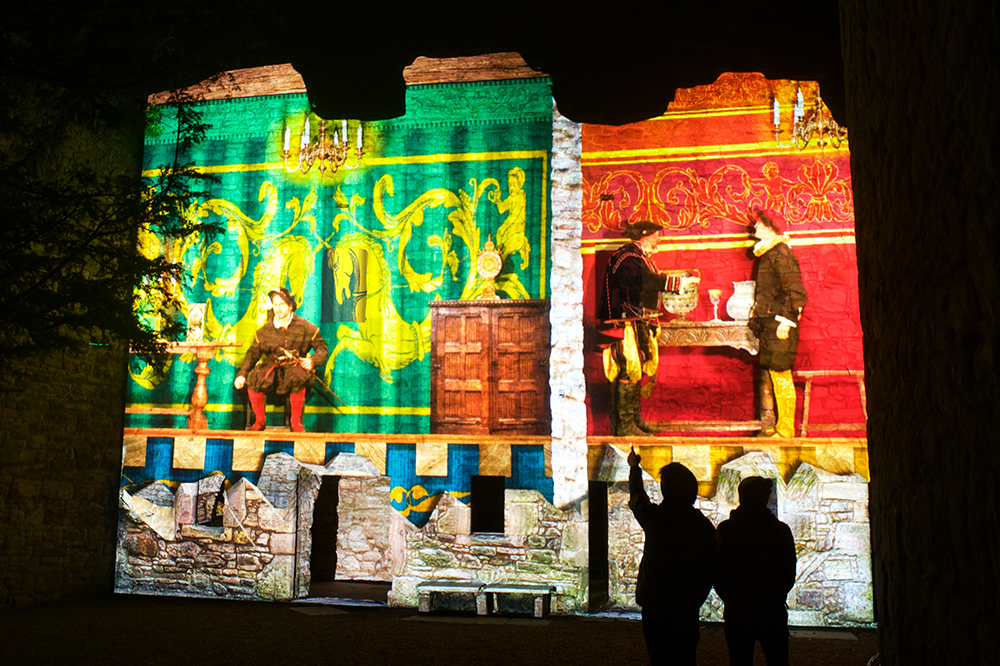 The silhouettes of two people watching a performance of Spotlight on Mary. The action is projected onto a castle wall. On the left hand side, a man with a sword sits at a table in front of a huge green tapestry featuring two gold unicorns. On the right, two men in 16th-century dress converse beneath a chandelier.