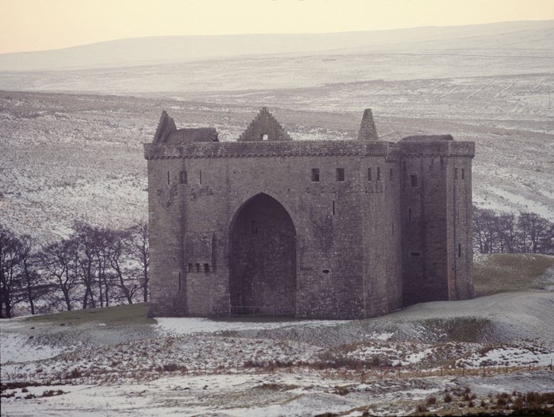 Wintry view of the imposing, hulking Hermitage Castle