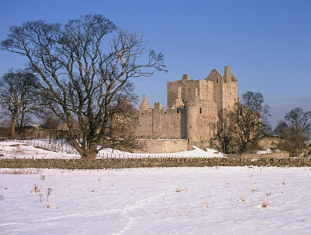 An exterior view of Craigmillar Castle. Snow is on the ground. Some footprints or animal tracks lead through the snow towards the castle.