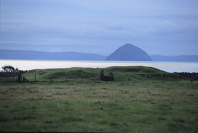 view of the cairn which sits on the seashore with a mountain behind