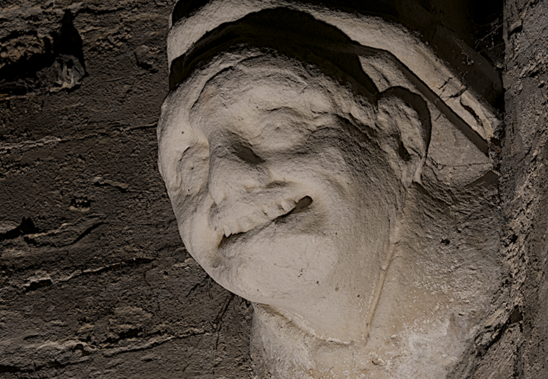 View from below of a spookily lit carving of a grimacing young man