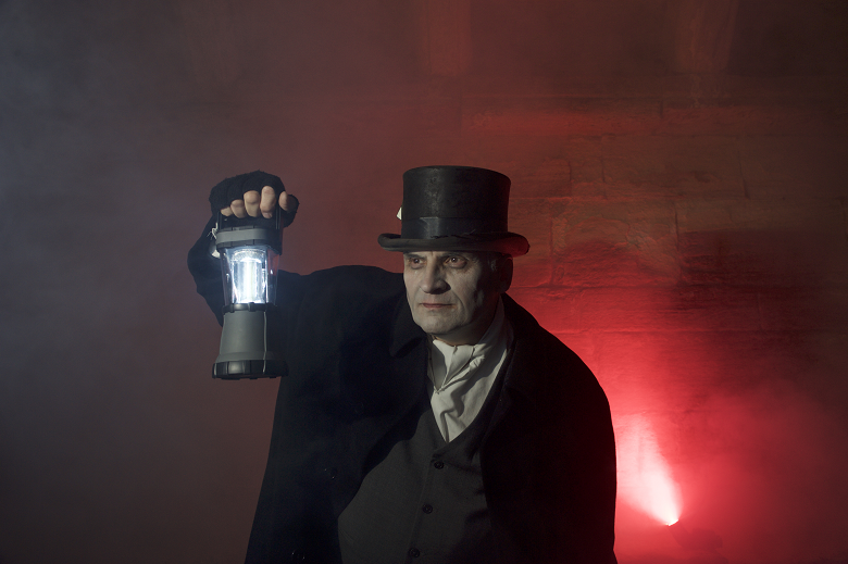 a ghoulish man in Victorian dress and top hat holds up a lantern
