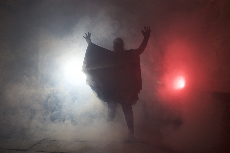A menacing cloaked figure stands silhouetted against some misty lights