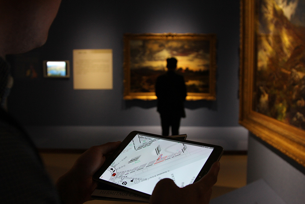A mobile application is being used inside a museum exhibition . A man can be seen studying a framed picture on the wall.