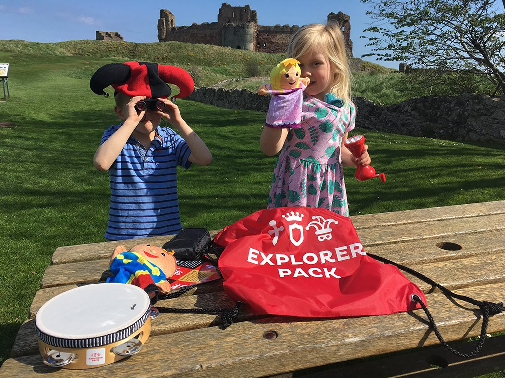 Two children standing in front of a castle with an explorer pack. One is wearing a jester's hat and using binoculars. The other has a hand puppet. A second hand puppet and a tambourine are beside the pack.