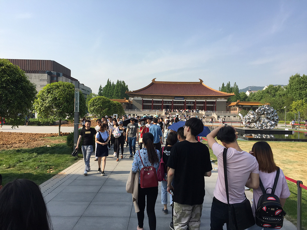 Visitors outside the Nanjing Museum in China. The museum has a distinctive red tiled roof. There is a silver sculpture and steps in front of the building.