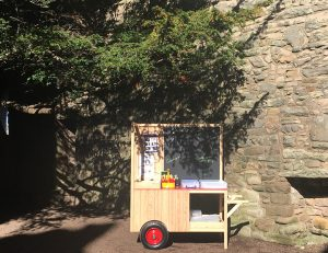 A wooden cart containing art equipment parked under a tree in a castle courtyard