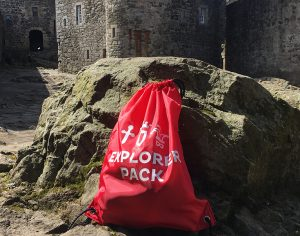 A red drawstring bag labelled Explorer Pack in front of a castle building.