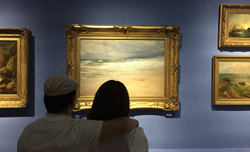 Two museum visitors are looking at a painting of a beach. The painting hangs in a gold frame.