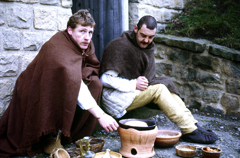 Two members of a Roman history reenactment group cook food over a replica North African style pot.