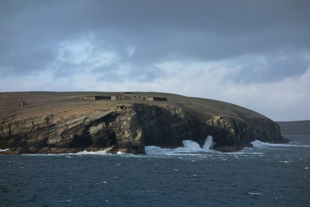 A view of Scapa Flow. Military defences can be seen on the clifftops. Large waves are battering the rocks below.