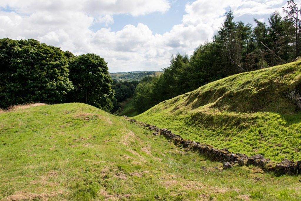 A general view of the Antonine Wall World Heritage Siite. The remains of a wall can be seen within a large ditch covered with grass.