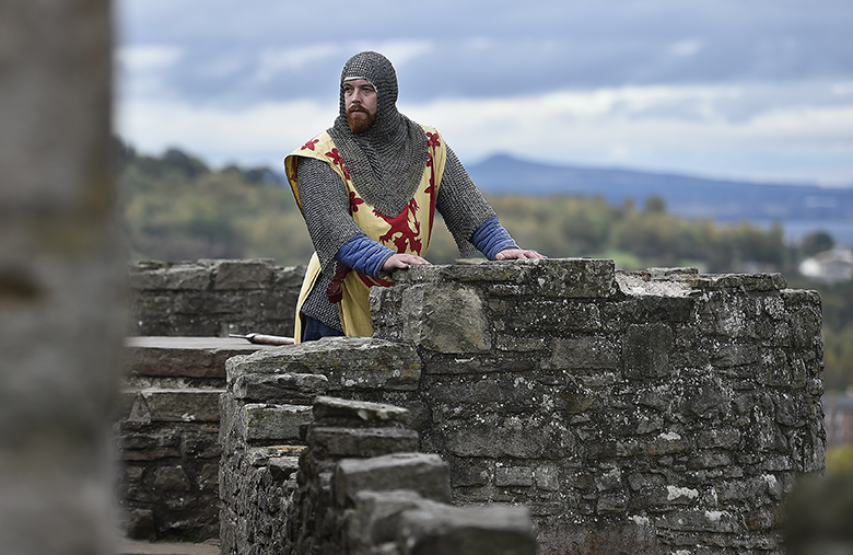 Man dressed as Robert the Bruce on castle battlements