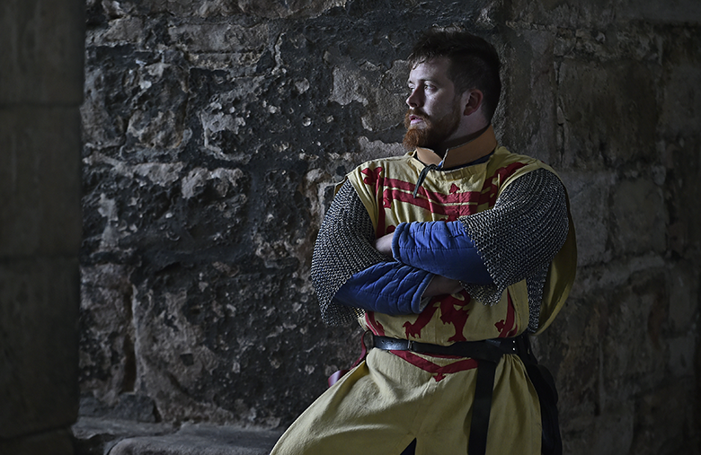 Man dressed as Robert the Bruce stares out of a castle window