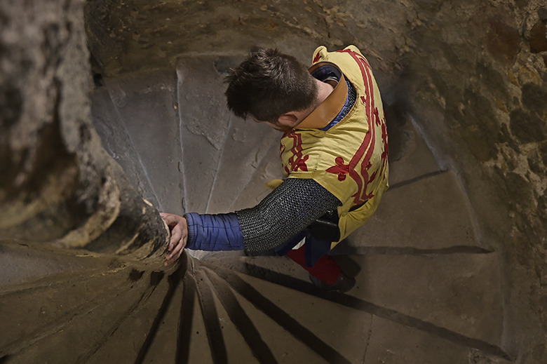 man dressed as Robert the Bruce descends a spiral staircase in a castle