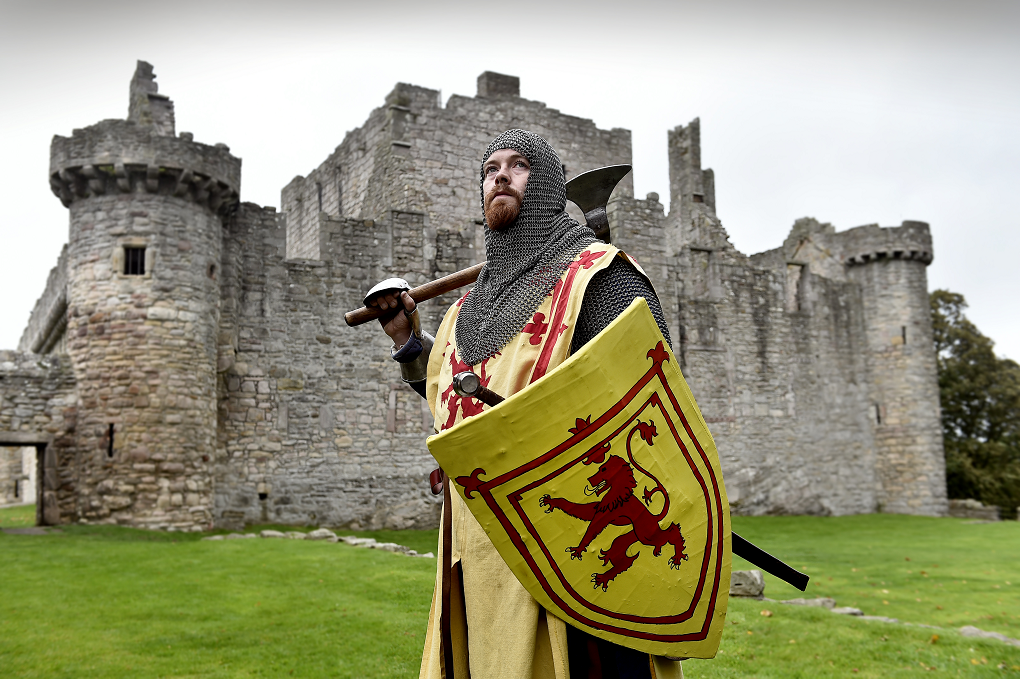 Man dressed as Robert the Bruce stands in front of Craigmillar Castle. He holds a shield with a Lion Rampant, in his other hand he holds an axe