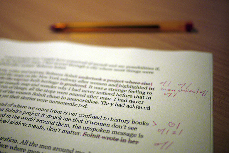 Close-up shot of a printed page being edited with red pen