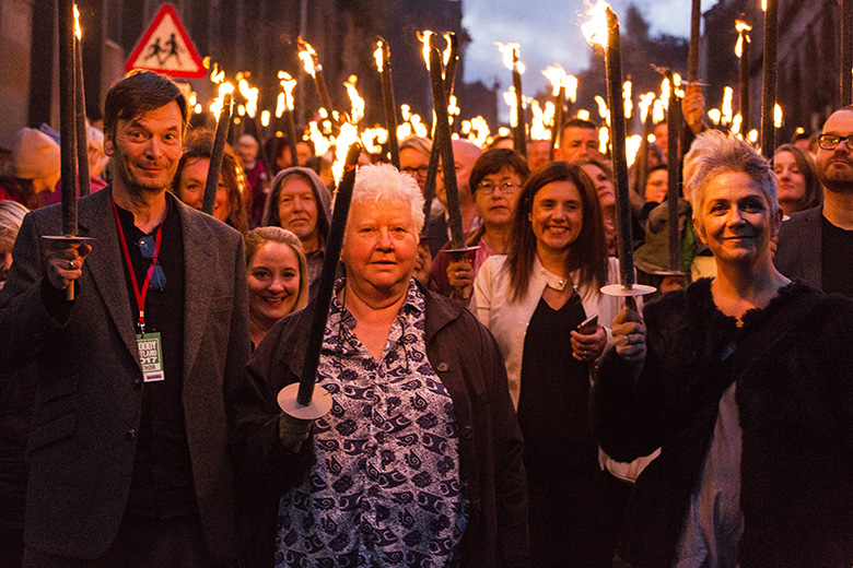 Authors pose in front of a crowd holding flaming torches