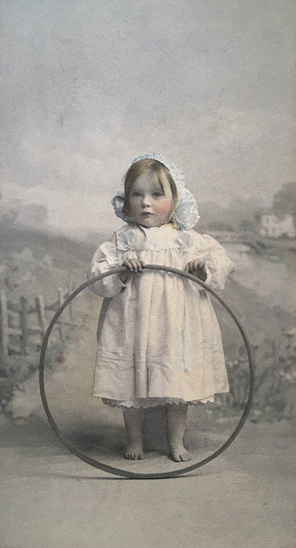 A Victorian painting of a young girl at play. She is barefoot, wearing a white dress and bonnet. She is holding a hoop.