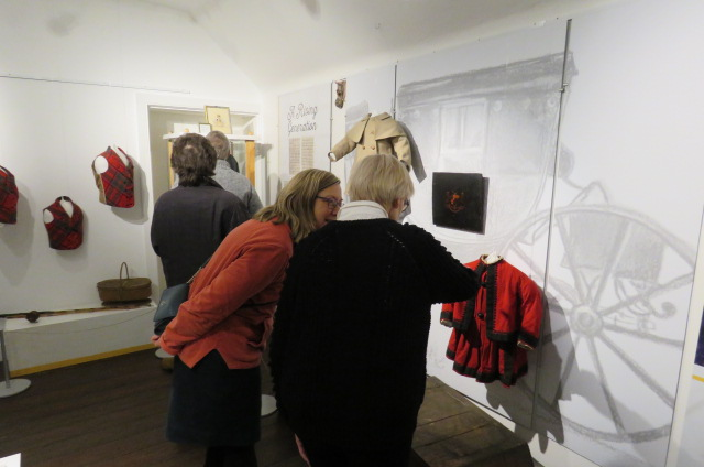 Visitors to the exhibition examine a display of Victorian clothing