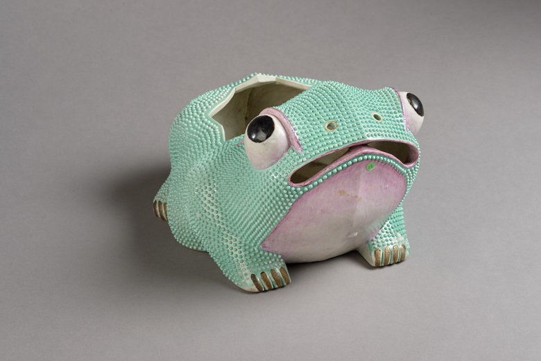 A green and pink ceramic flower holder in the shape of a frog. The frog is looking upwards with a bewildered expression on its face. Part of the collections at Duff House.