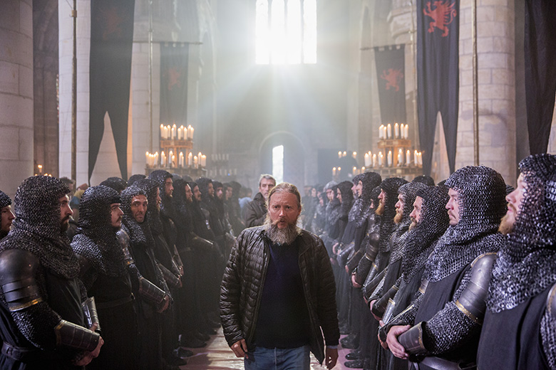 The director of Outlaw King walks between two lines of extras, dressed as medieval soldiers, in Dunfermline Abbey.