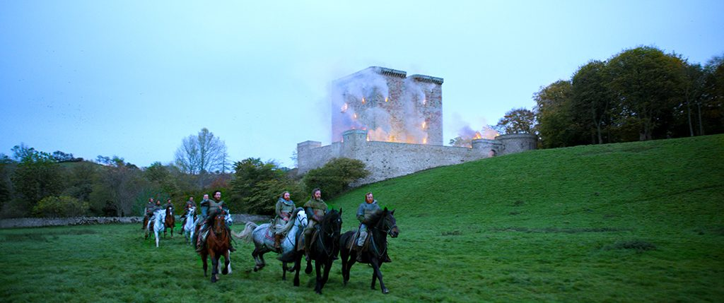 A still from the Outlaw King film. Nine medieval soldiers on horseback ride away from a burning castle.