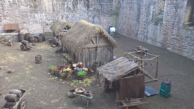 Doune Castle courtyard transformed into a film set. Thatched huts and props, including food and barrels, can be seen.