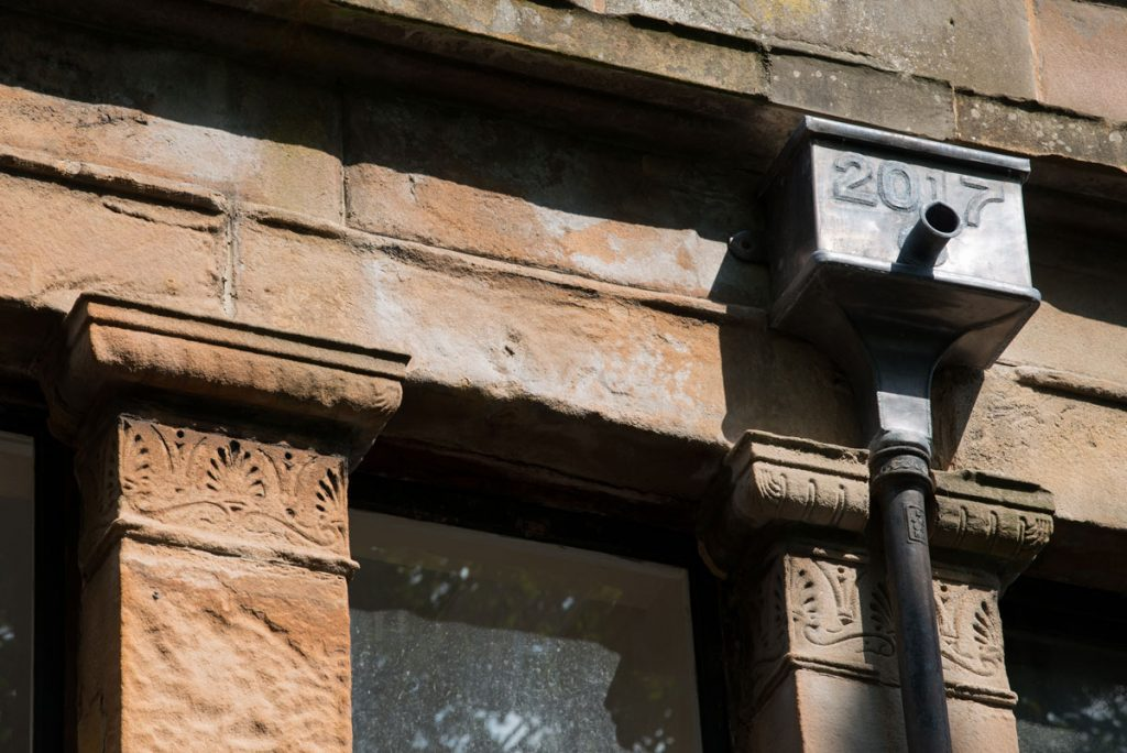 Details of carved red sandstone blocks and a downpipe on the side of a building.