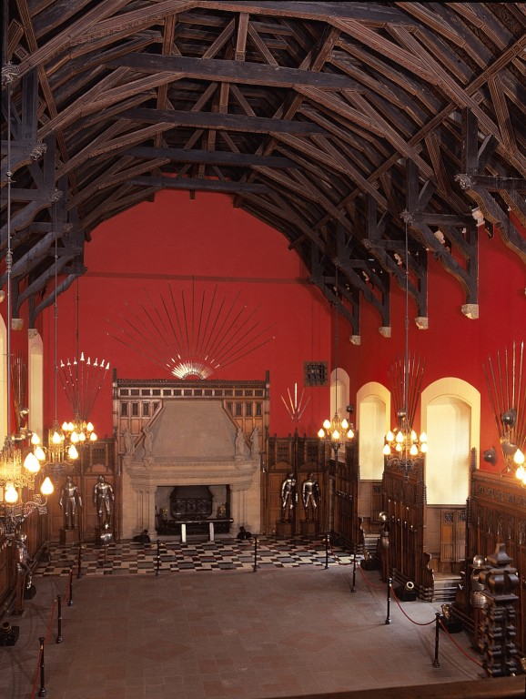 Interior view of the great hall at Edinburgh Castle. There is a distinctive timber roof and striking red walls.