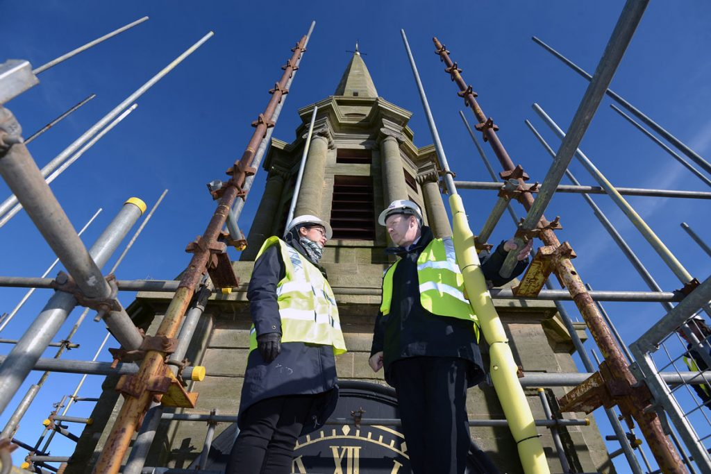 A man and a woman in high visibility jackets standing on scaffolding mounted around a church steeple on a sunny day