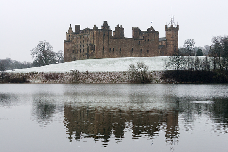 View of Linlithgow Palace across the loch on a snowy day
