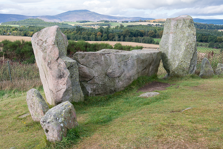 View of two upright stones flanking a large recumbant stone. This frames the landscape behind.