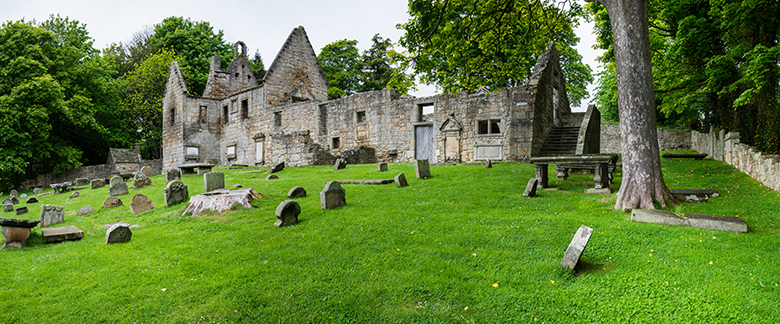 View across a graveyard to a ruined church