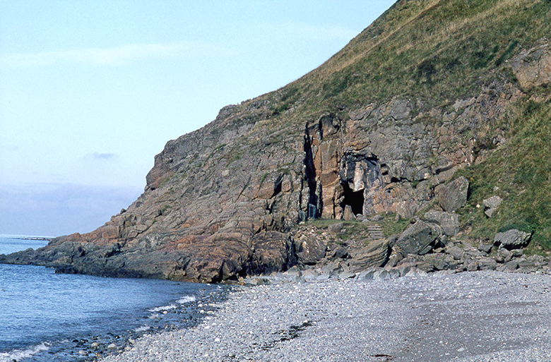 View across a pebble beach to a rocky outcrop where there is the mouth of a cave