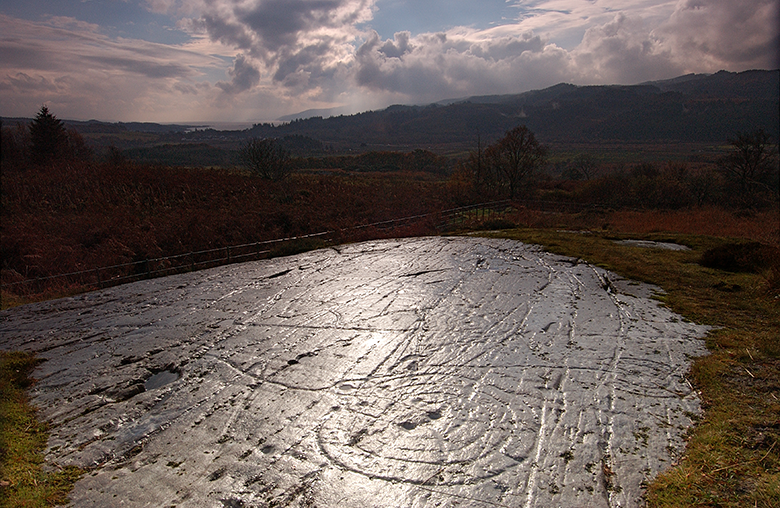 View of a flat rock surface carved with prehistoric markings. You can see the beautiful landscape of the glen beyond.