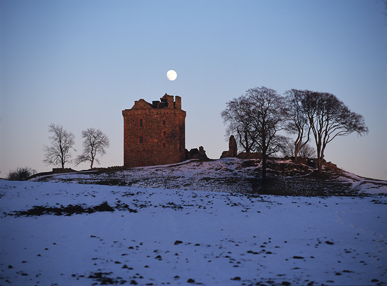View of the castle at twilight in the snow. The moon hangs just above it and trees are silhouetted against the sky.